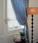 床まで届くゆったりとしたドレープカーテンとプレーンシェードの組み合わせ